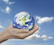 Earth in hands over blue sky with white clouds, Environment conc Royalty Free Stock Photography