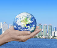 Earth in hands over city tower and river background, Environment Royalty Free Stock Photography