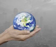 Earth in hands over pollution city, Environment concept, Element Royalty Free Stock Photo