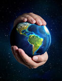 Earth in the hands - USA, space. Planet whit universe background stock photo