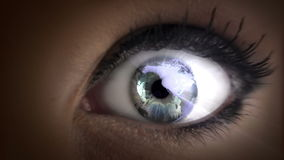 Earth in her eyes. Looping video direct close up shot of a woman with graphical earth rotating in her eyes