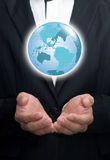 Earth in his hands. Holding a glowing earth globe in his hands Royalty Free Stock Photography