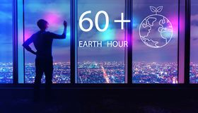 Earth hour with man by large windows at night. Earth hour with man writing on large windows high above a sprawling city at night royalty free stock photos