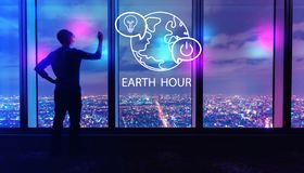 Earth hour with man by large windows at night. Earth hour with man writing on large windows high above a sprawling city at night stock images