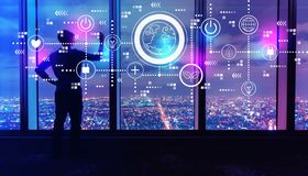 Earth hour with man by large windows at night. Earth hour with man writing on large windows high above a sprawling city at night stock image