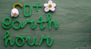 Earth hour message on green background. For special day, a day to remind people give hand save the earth, green letter with white flower symbol for turn off Royalty Free Stock Photography