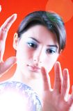 Earth Keeper. Young serious woman with hands poised over a glowing replica of the earth. Isolated on an orange background stock photo