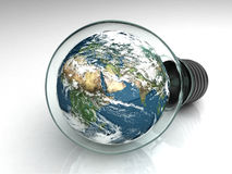 Earth in a light bulb. Planet Earth floating in a light bulb sitting on a table Royalty Free Stock Image