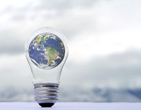 An earth in a lightbulb on a natural background Stock Photography