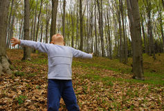 Earth lungs. A boy is standing in the woods with arms spread, breathing the air Royalty Free Stock Photo