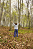 Earth lungs. A boy is standing in the woods with arms spread, breathing the air Stock Photos
