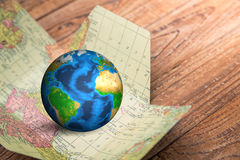 Earth in map  on wood background Elements of this image furnishe Stock Photos