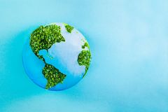 Earth model made of paper and fresh green sprouts collage on blue background. Green planet creative concept. Earth day. Selective. Focus, space for text royalty free stock photography