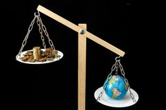 Earth and Money on a Two Pan Balance Royalty Free Stock Photos
