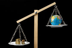 Earth and Money on a Two Pan Balance Royalty Free Stock Photo