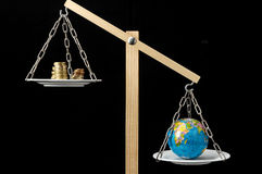 Earth and Money on a Two Pan Balance Royalty Free Stock Images