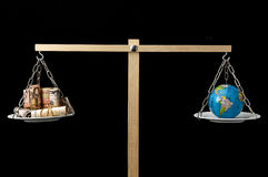 Earth and Money on a Two Pan Balance Stock Photos