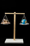 Earth and Money on a Two Pan Balance Royalty Free Stock Photography
