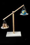 Earth and Money on a Two Pan Balance Royalty Free Stock Image