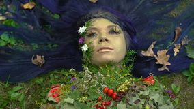 Earth mother in flowering decoration lying on grass, nature as living being. Stock footage stock footage