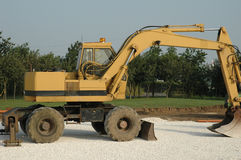 Earth mover. A yellow mechanical digging vehicle on a construction site Stock Images