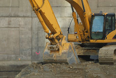 Earth mover. A large yellow earth mover in front of a wall Royalty Free Stock Image