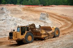 Earth mover. Heavy earth mover at a construction site stock photo