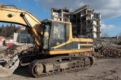 Earth mover demolishing ruins Stock Image