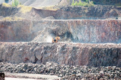 Earth mover driving around in a surface mine quarry Stock Images