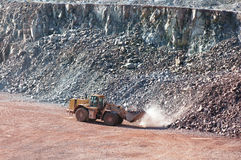 Earth mover driving around in a surface mine quarry Stock Photo