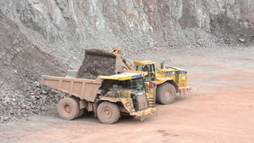 Earth mover loading a dumper truck with stones in a quarry, surface mine. typical mining industry. Located at Bebertal on April 12, 2014 stock footage