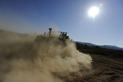 Earth-mover making dust. A large earth-mover under a hot sun, leaving trail of dust Stock Images