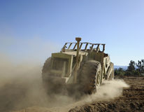 Earth-mover making dust. A large earth-mover under a blue sky, leaving trail of dust Royalty Free Stock Photo