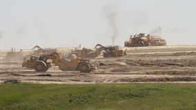 Earth movers in new housing development. Large earth movers preparing the ground for a new housing development stock footage