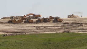 Earth movers in new housing development. Large earth movers preparing the ground for a new housing development stock video footage