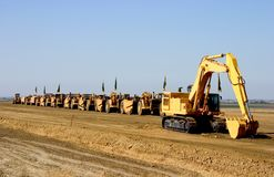 Earth Movers on Parade. A parade of giant earth-movers are led by a giant mechanical shovel stock photos