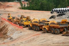 Earth moving equipment on parade. Heavy earth moving construction vehicles lined up in a row stock photography