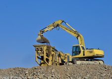 Earth moving excavator in action. Excavator loading soil into large spreading container Stock Images