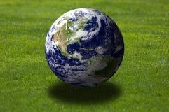 Earth over grass field Stock Photos