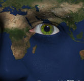 Earth painted on face with green eye. Elements of this image furnished by NASA Royalty Free Stock Photo