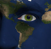 Earth painted on face with green eye. Elements of this image furnished by NASA Stock Photo