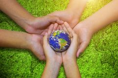 Earth planet in  asian Children hand green grass background Royalty Free Stock Photos