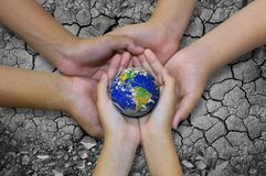 Earth planet in asian Children hand isolated on Ground arid barr Royalty Free Stock Photo