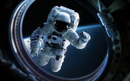 Earth planet and astronaut in space ship window porthole. Elements of this image furnished by NASA