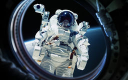 Earth planet and astronaut in space ship window porthole. Elements of this image furnished by NASA Stock Images