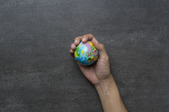 Earth planet in female hand on black background Royalty Free Stock Photos