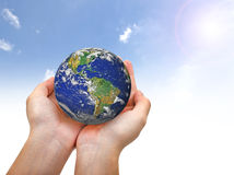 Earth planet in female hand and blue sky Royalty Free Stock Image