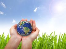 Earth planet in female hand and blue sky. Elements of this image furnished by NASA Stock Image