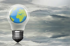 Earth planet inside light bulb over dark skyline Stock Image