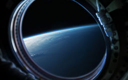 Earth planet in space ship window porthole. Elements of this image furnished by NASA. Earth planet and astronaut in space ship porthole. Elements of this image Royalty Free Stock Photos